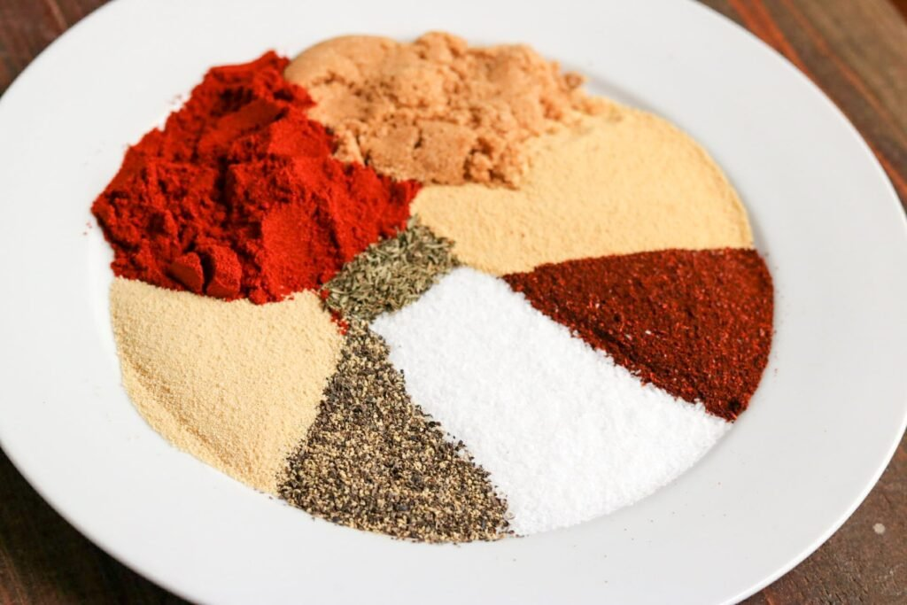 Dry rub ingredients in separate piles on white plate.