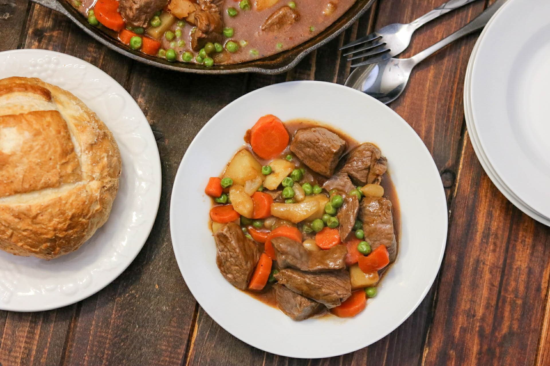 Overhead shot of beef and Guinness stew in white bowl with roll on white plate and remaining stew in cast iron skill on the side, all on a wood table.