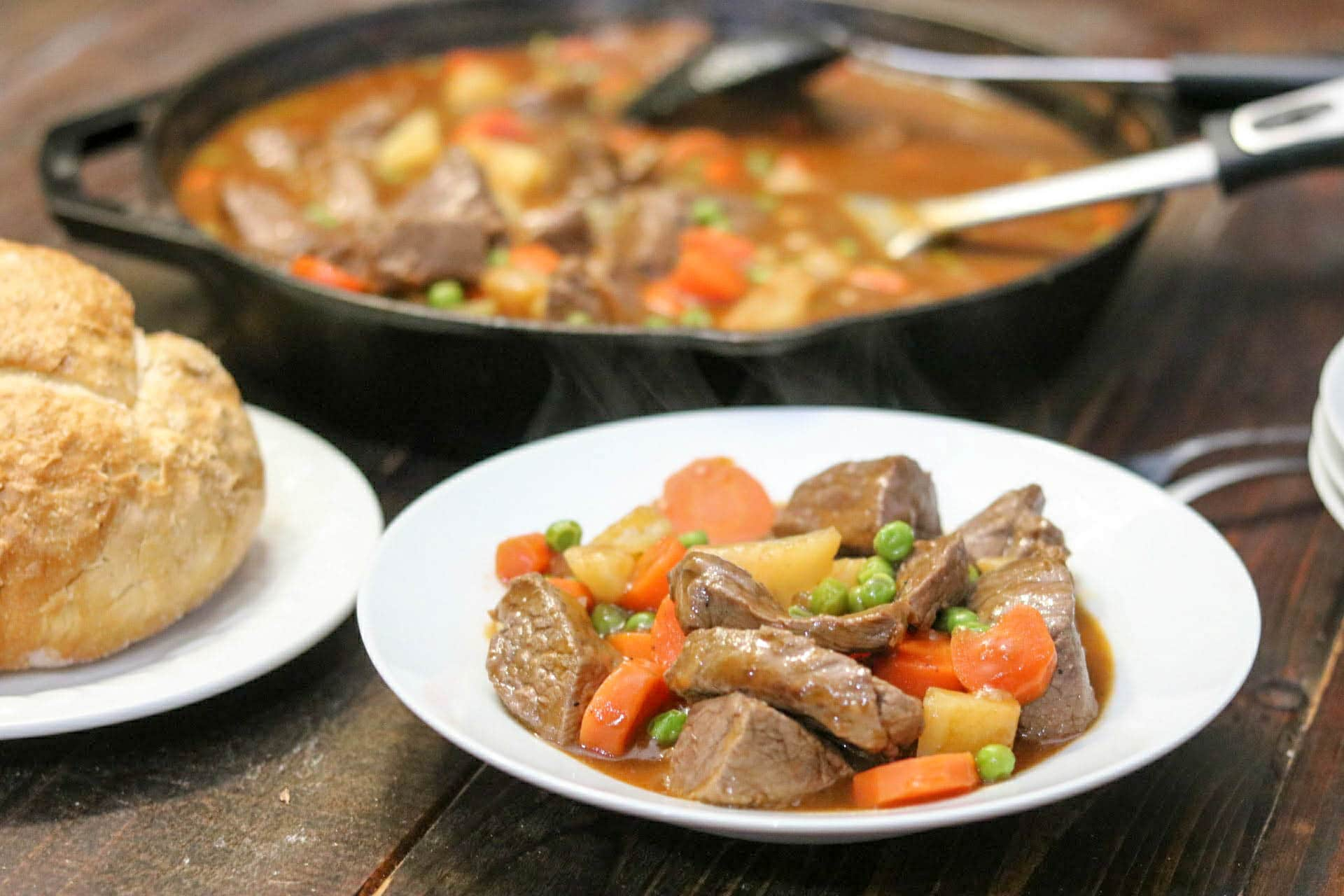Beef and Guinness stew in white bowl with roll on white plate and remaining stew in cast iron skillet in background on wood table.
