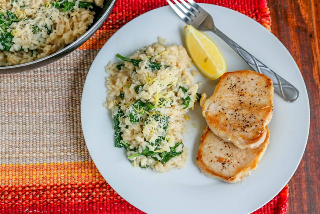 risotto on a white plate with lemon, and pork chops