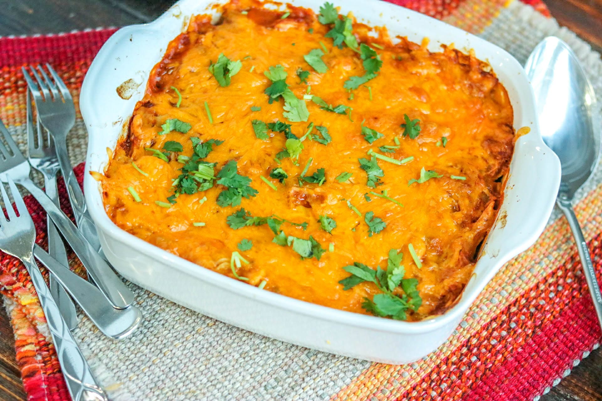 Cheesy chicken enchilada pasta in white bakeware with forks and spoon on the side on a tweed mat.