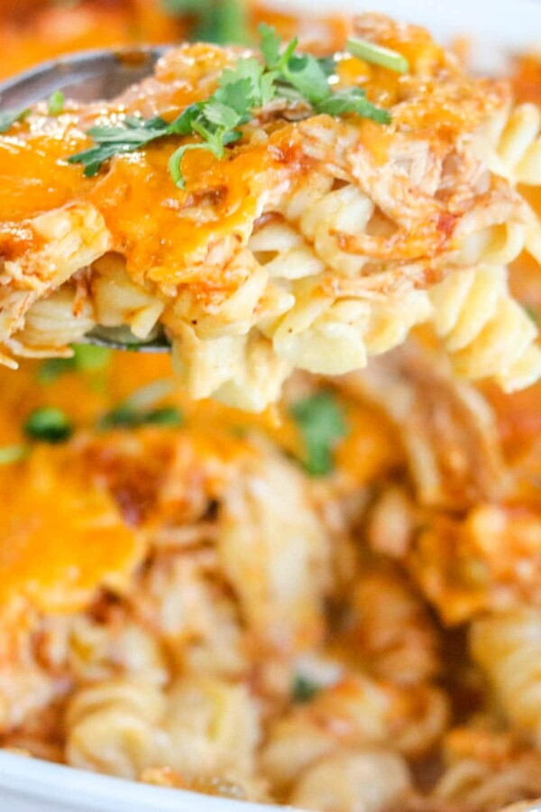 close up spoon shot of chicken enchilada pasta in a white baking dish