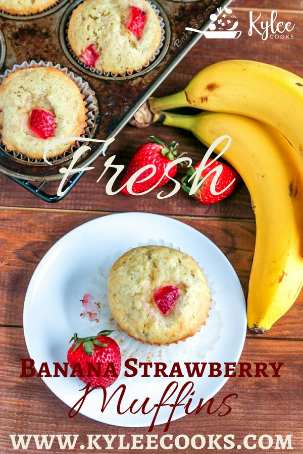 Fresh strawberry banana muffins in baking tin and one muffin on white plate with strawberries and bananas on the side on wooden table.
