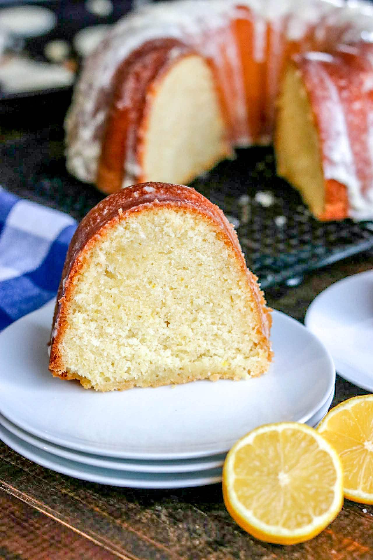 glazed lemon bundt cake slice on a plate with cut lemon and a blue napkin