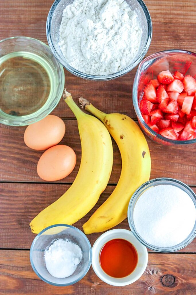 Overhead shot of bananas, eggs, diced strawberries in glass bowl, and remaining ingredients in individual bowls on wooden table.