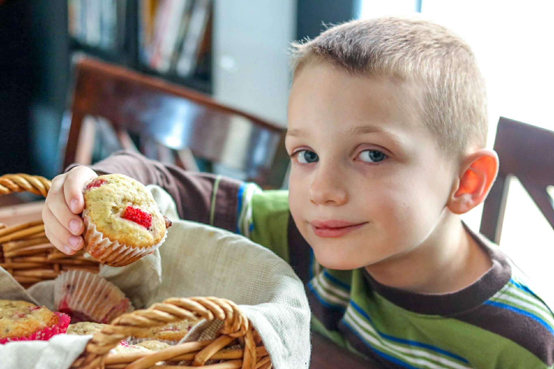 Boy holding strawberry banana muffin over wicker basket lined with towel and filled with more muffins.