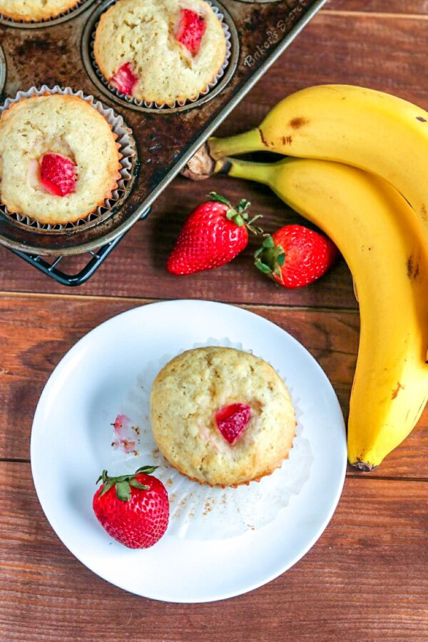 strawberry banana muffin on a white plate with a banana and strawberry on the side
