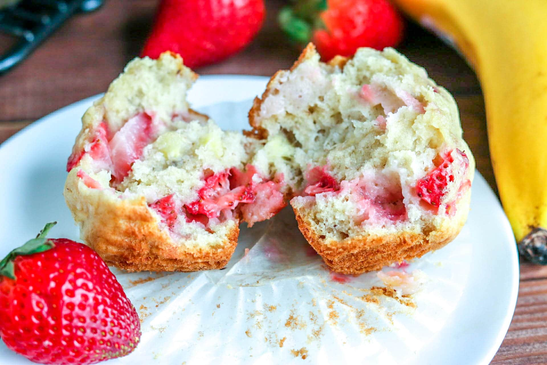 Fresh strawberry banana muffin pulled in half with strawberry on white plate with banana and strawberries in background on wooden plate.