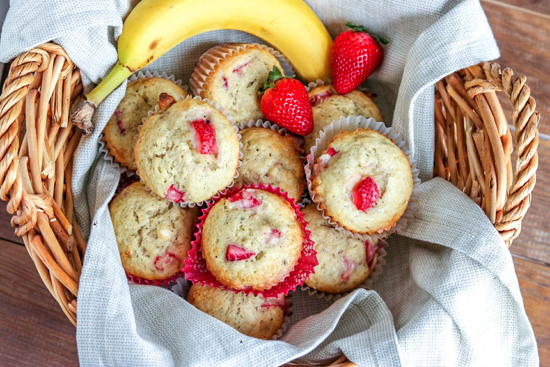 Fresh strawberry banana muffins with strawberries and banana in wicker basket lined with blue towel on wooden table.