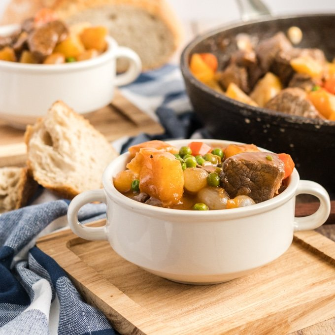 guinness beef stew in a white bowl with crusty bread