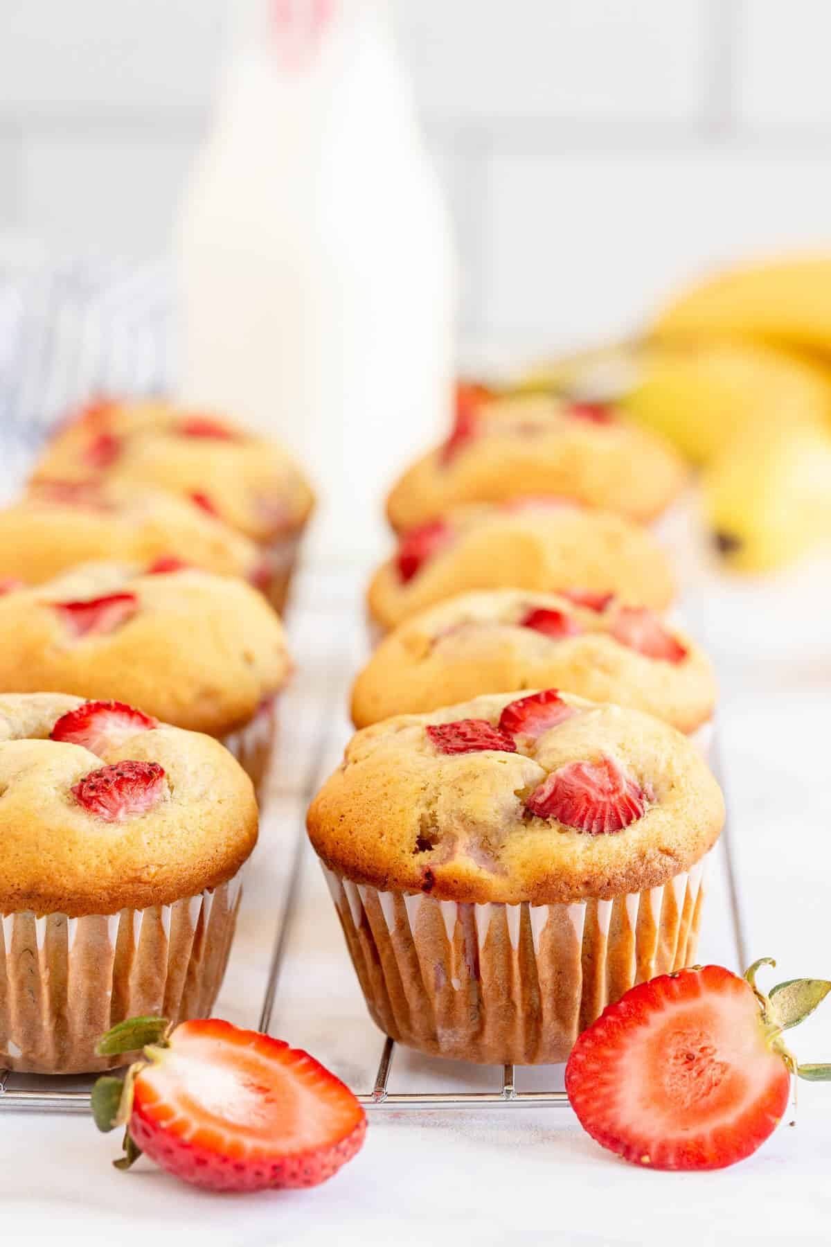 strawberry muffins with a bottle of milk in the background