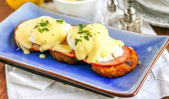 Breakfast for EVERYONE! A super easy recipe for Gluten Free Eggs Benedict that will please the whole family. Crispy hash browns, topped with Canadian bacon, perfectly poached eggs and a rich hollandaise sauce - yum!