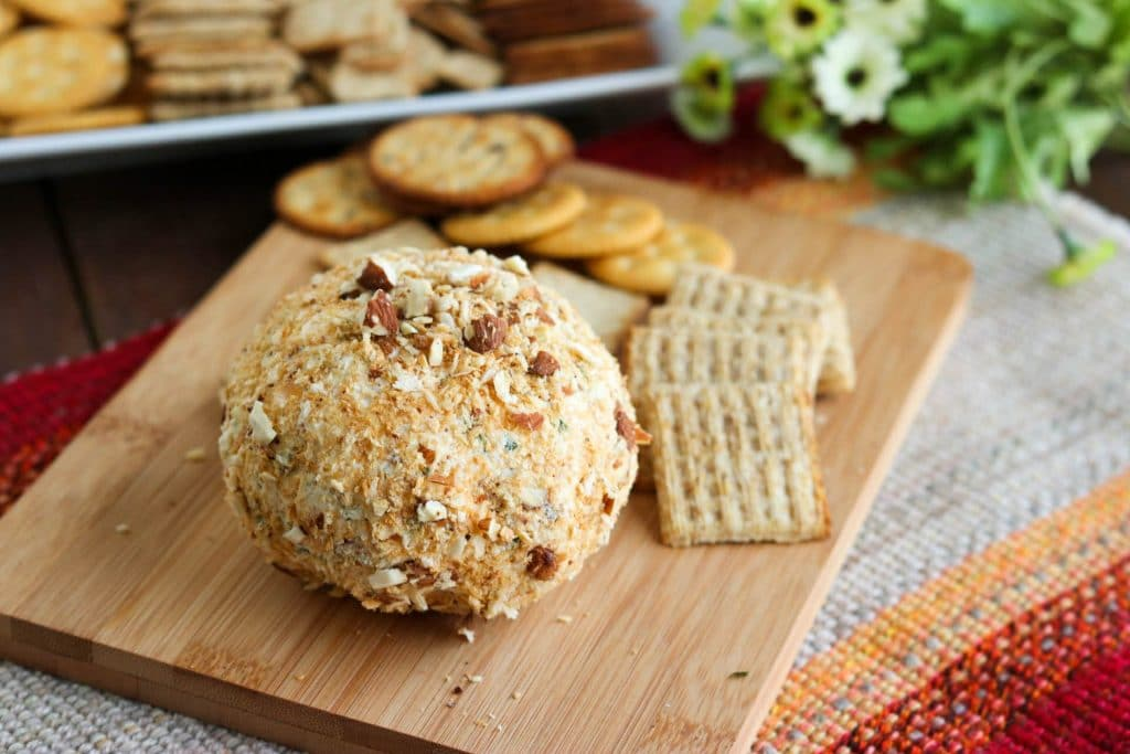 Jalapeno popper cheese ball with crackers on wooden cutting board sitting on tweed mat.