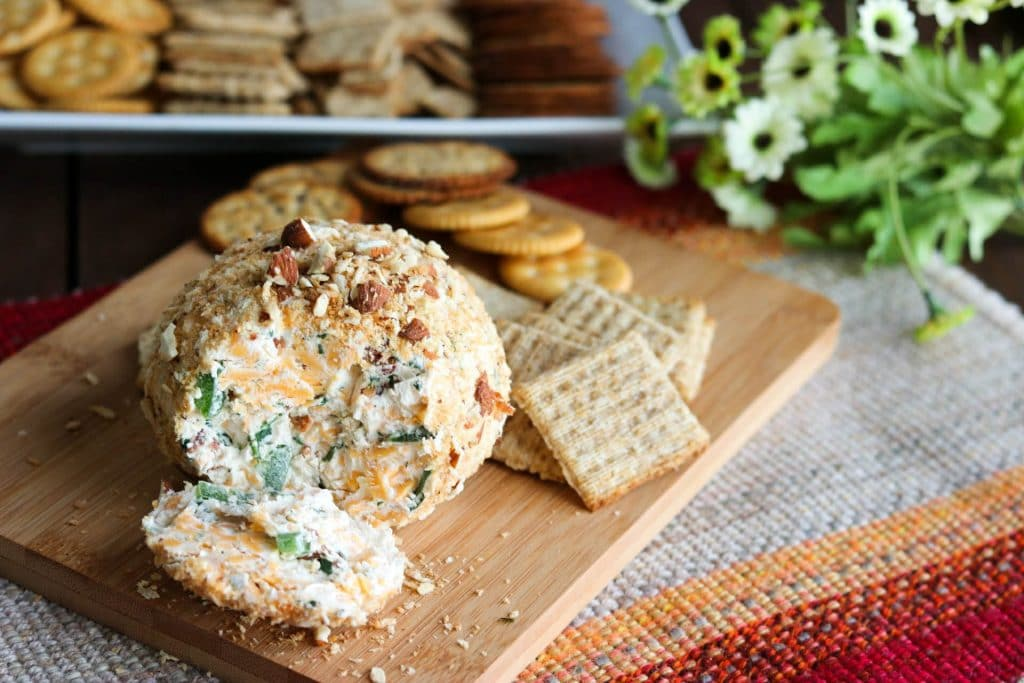 Jalapeno popper cheese ball with piece removed to show inside and crackers on wooden cutting board on tweed mat with tray of crackers in background.