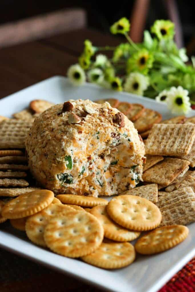 jalapeno popper cheese ball on a white platter, with crackers