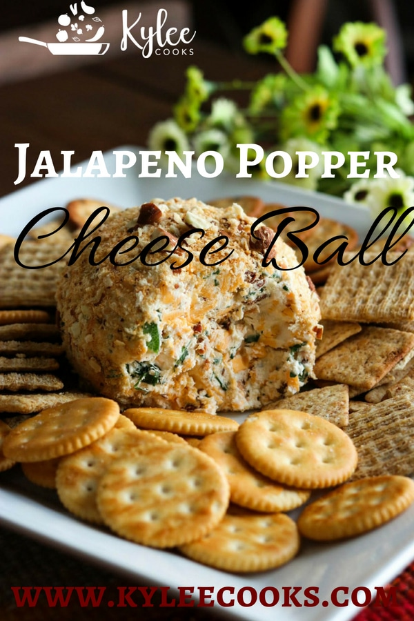 Jalapeno popper cheese ball with piece taken out surrounded by crackers on white serving plate.