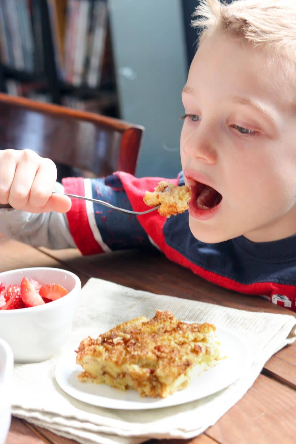 A little boy eating baked french toast