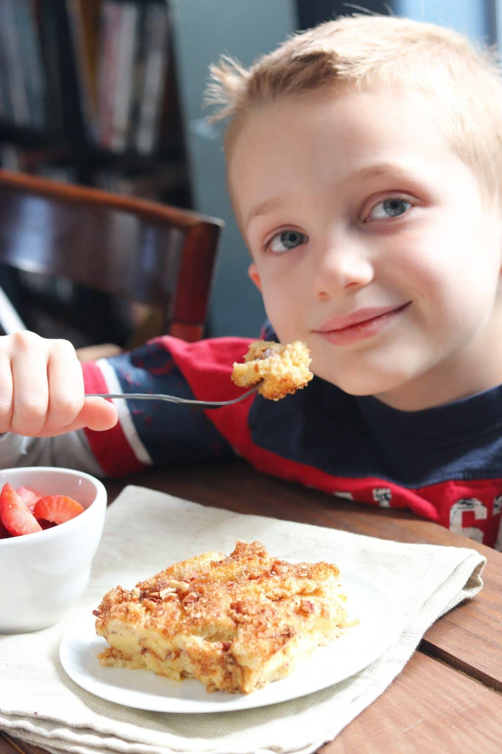 A little boy sitting at a table eating food baked french toast