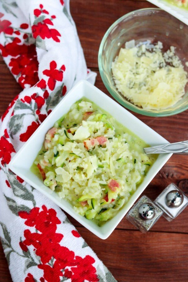 zucchini risotto in a square bowl with a red flowered towel