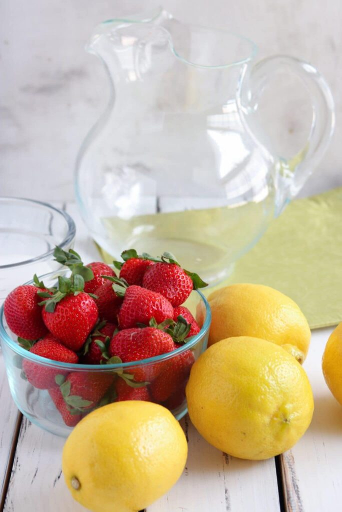 Glass bowl of strawberries surrounded by three lemons with glass pitcher in background on white wooden table.