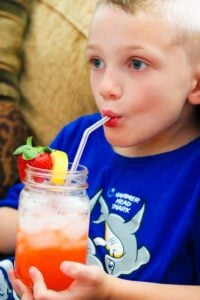 Little boy in blue shirt drinking strawberry lemonade with a straw.