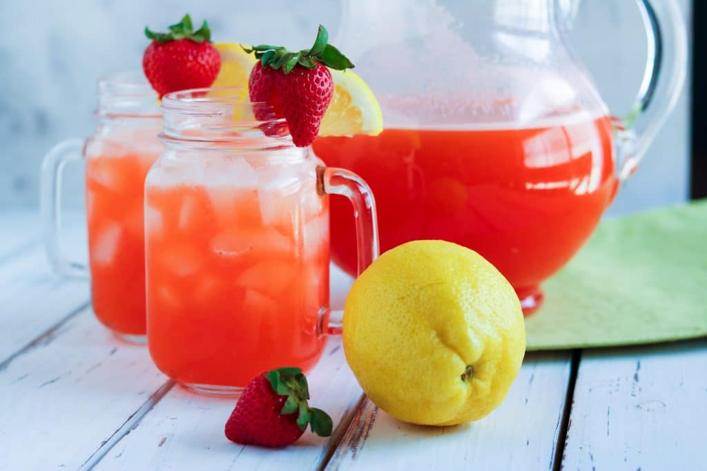 Two mason jar mugs filled with strawberry lemonade and garnished with a strawberry and lemon wedge sitting in front of a glass pitcher filled with more strawberry lemonade, all on a white wooden table.