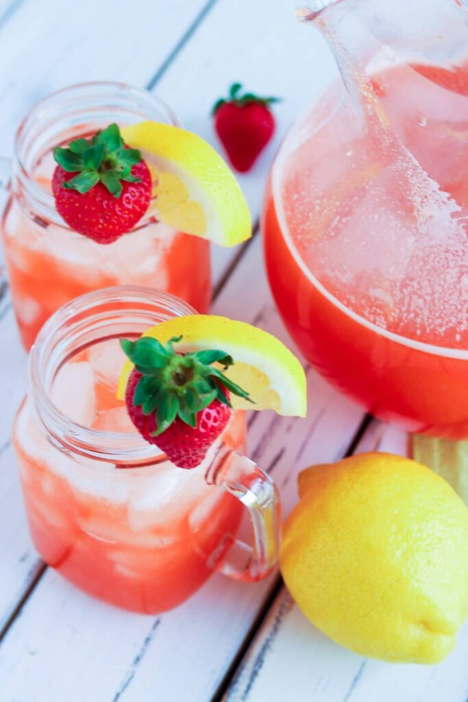 Two lemon and strawberry garnished mason jar mugs and serving pitcher all filled with strawberry lemonade and sitting on a white painted wood table.