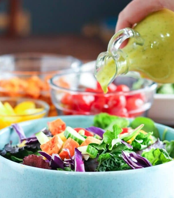 mango salad dressing being poured on a salad from a glass cruet