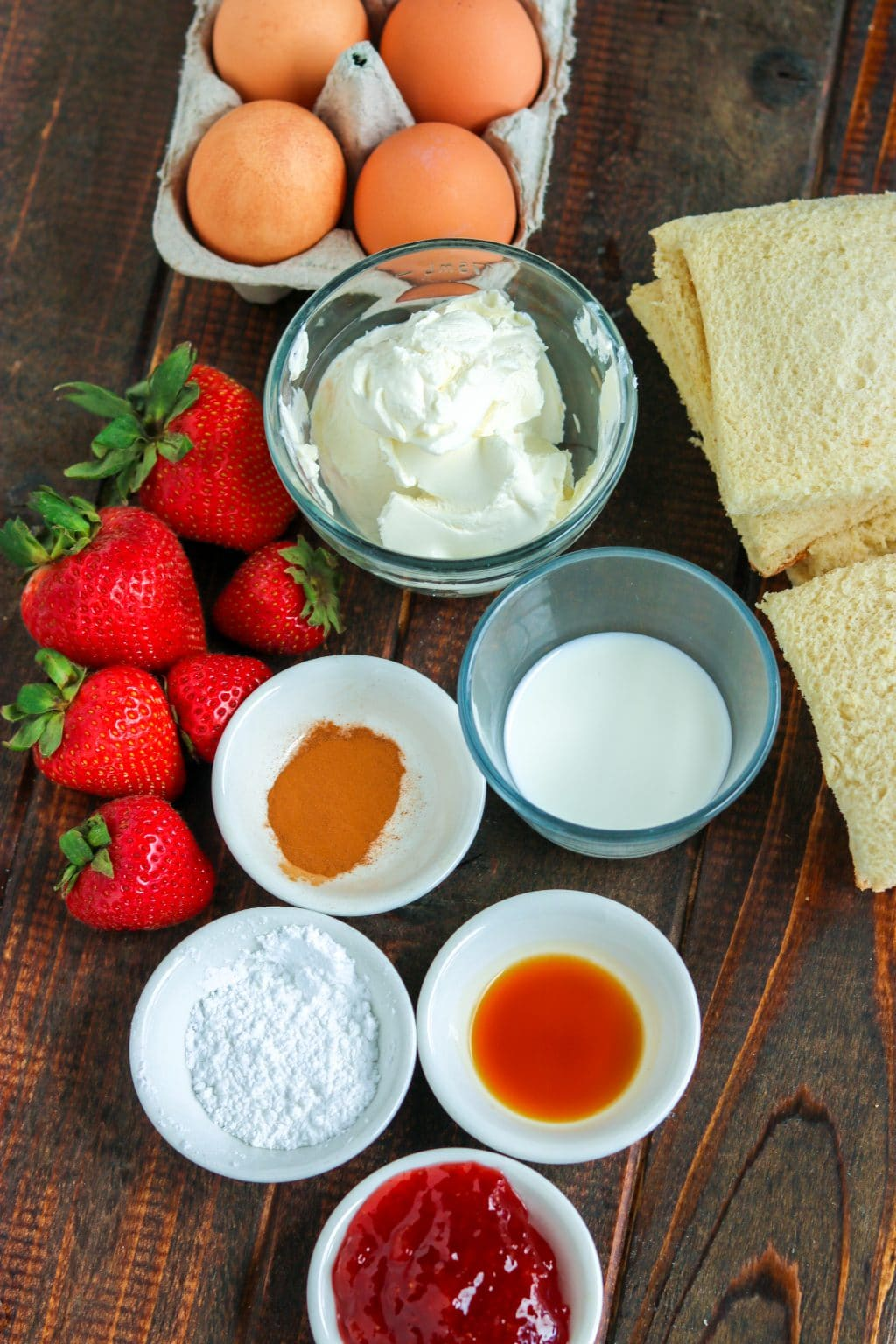 Ingredients for strawberry cheesecake French toast rolls in individual bowls, strawberries, eggs in a carton, and bread slices on wooden table.