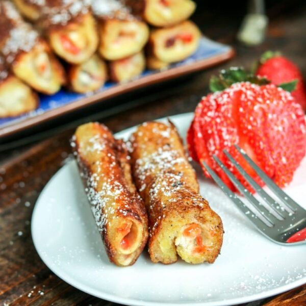 french toast roll ups on a plate with strawberries