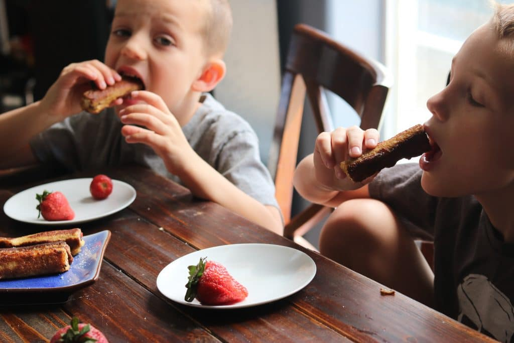 Two boys enjoying strawberry cheesecake French toast rolls while seated at wood table.