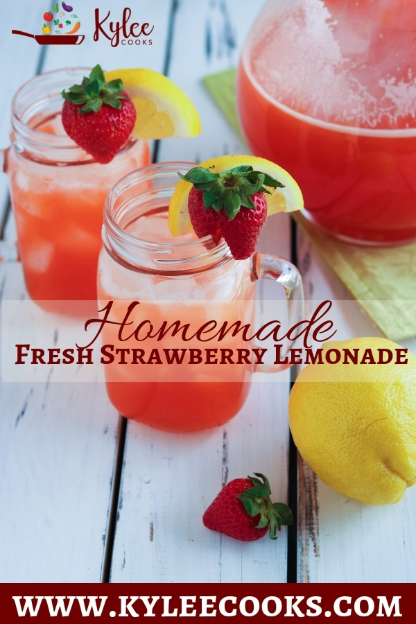 Two mason jar glasses with strawberry lemonade with a pitcher of strawberry lemonade, lemon, and strawberry on the side all on a white painted table.