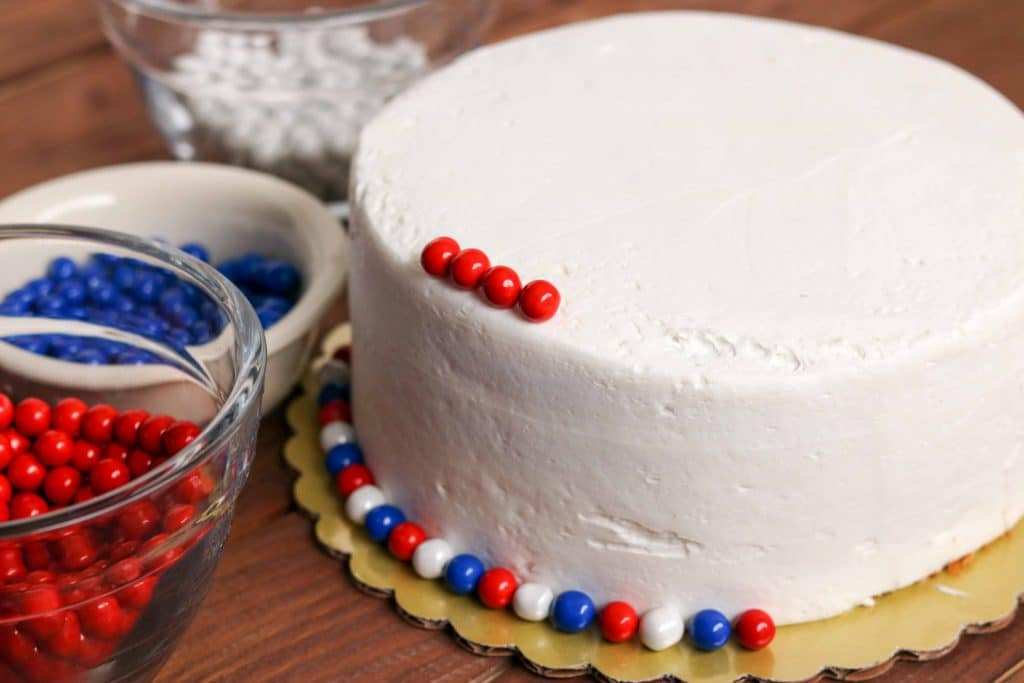 Closeup shot of cake frosted with white icing with red, white, and blue candies being added for decoration.