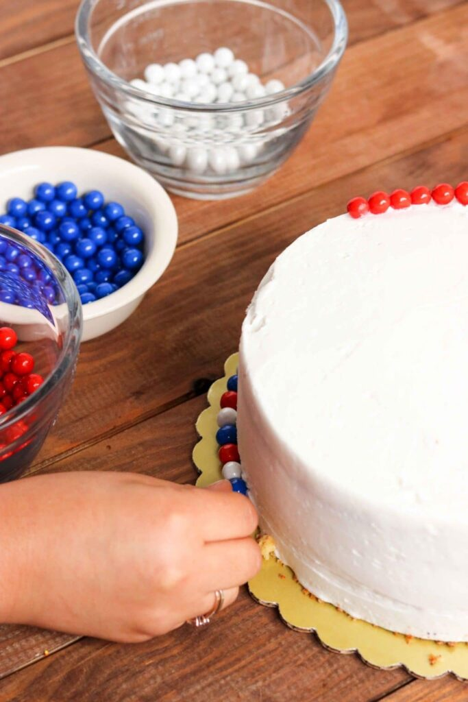 Closeup shot of decorating white frosted cake with red, white, and blue candies.