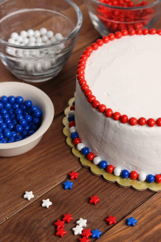 Close up shot of white frosted cake with red, white, and blue candies bordering bottom and red candies bordering top.