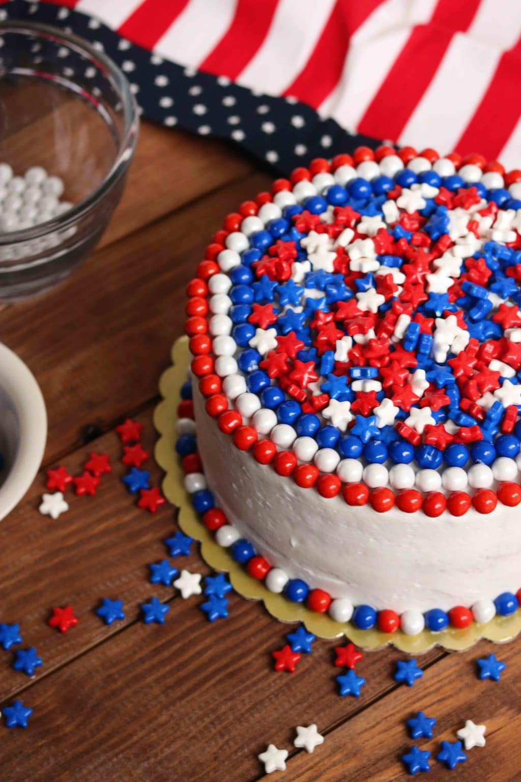 Red, white, and blue cake surrounded by red, white, and blue star-shaped candies on wooden table.