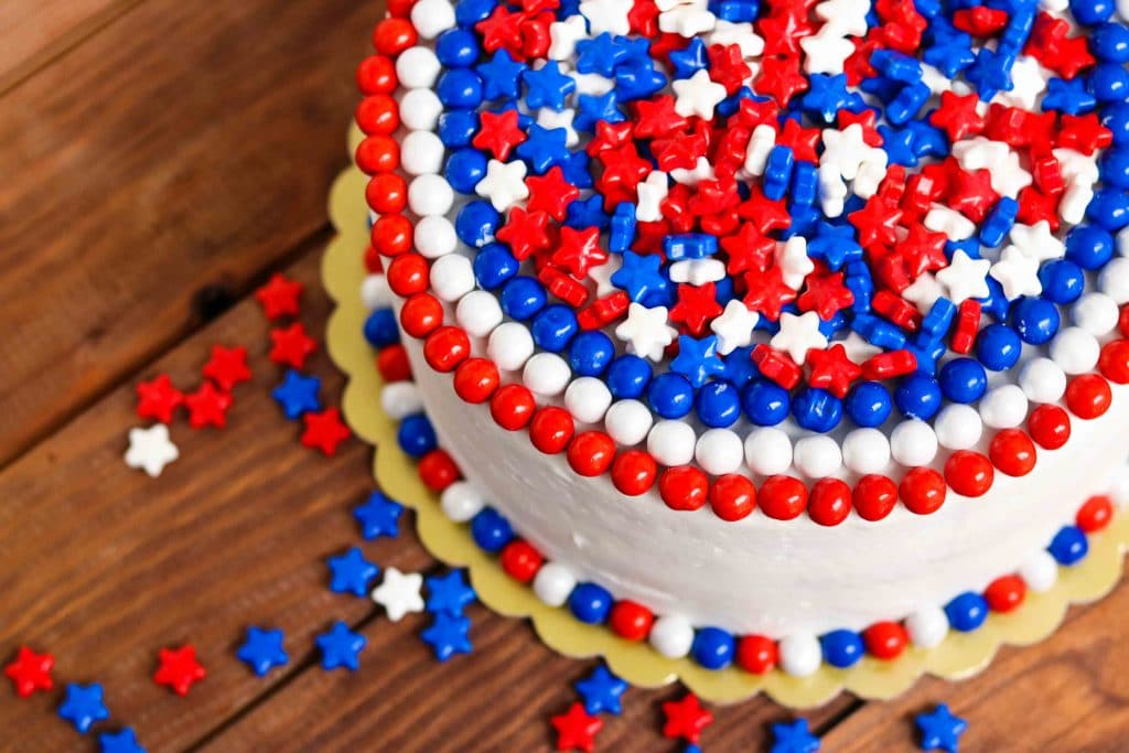 Closeup of red, white, and blue cake surrounded by red, white, and blue star-shaped candies on wooden table.