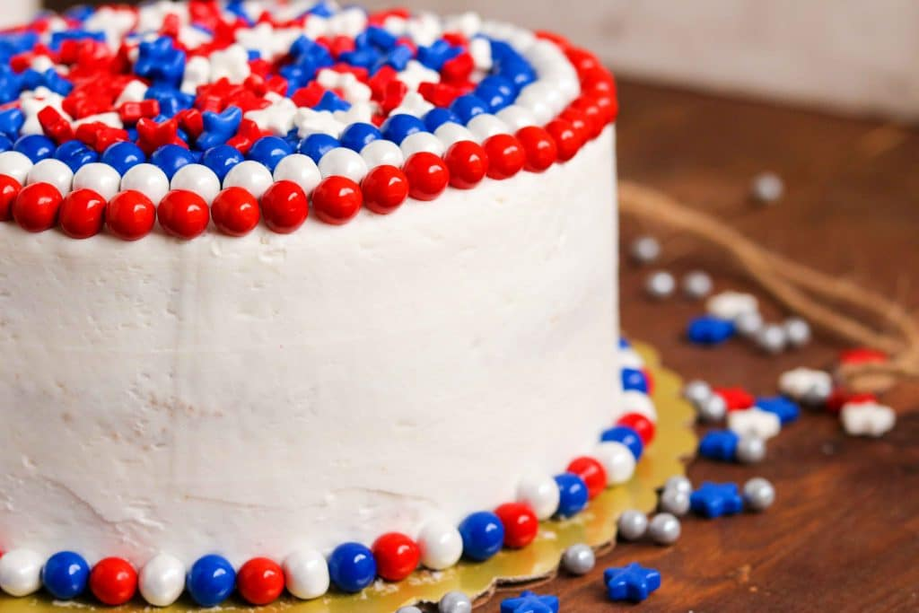 Closeup of finished red, white, and blue cake surrounded by red, white, and blue candies on wooden table.