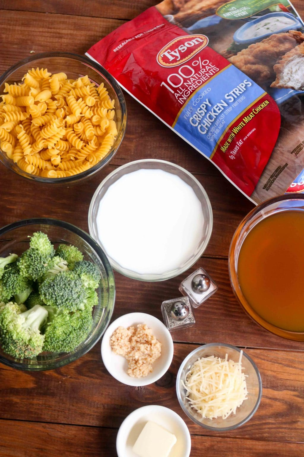 Individual ingredients for Broccoli Chicken Alfredo Pasta in bowls along with Tyson crispy chicken strips package on a wooden table.