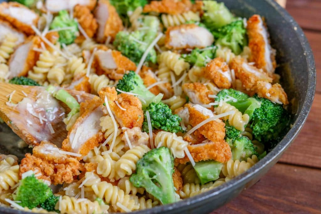 Closeup of spooning out Broccoli Chicken Alfredo Pasta from the pan.