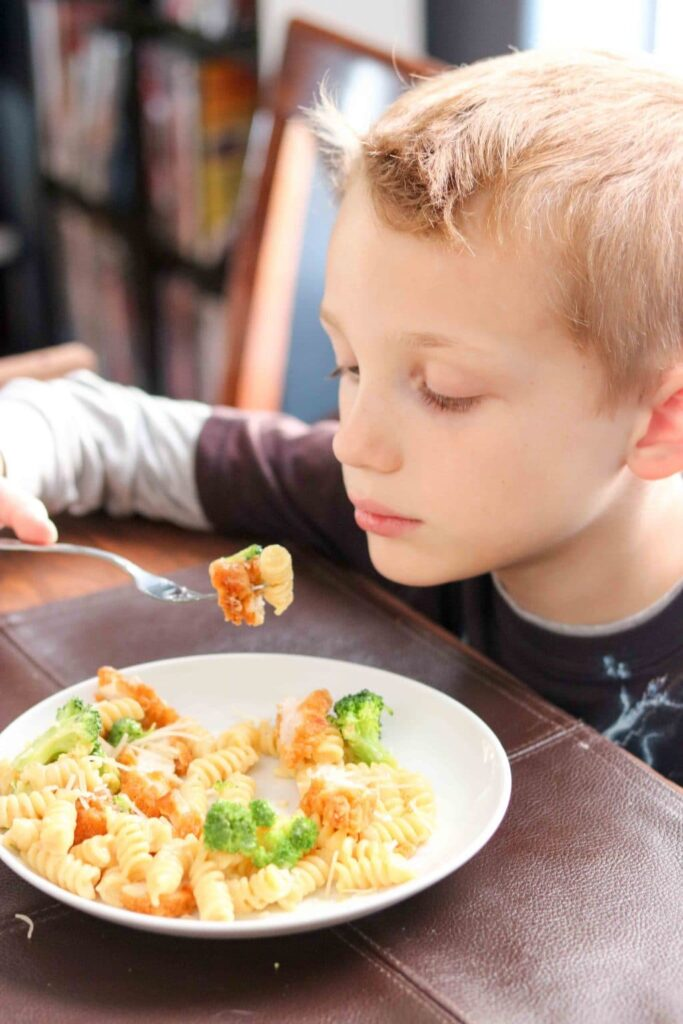 Boy holding a forkful of Broccoli Chicken Alfredo Pasta.
