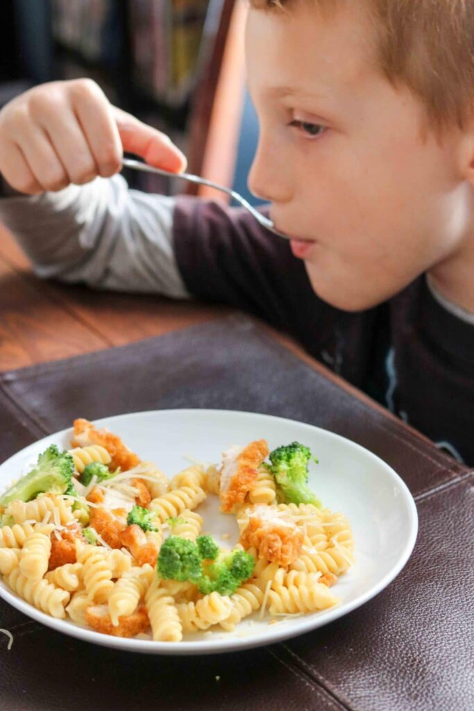 Boy eating Broccoli Chicken Alfredo Pasta.