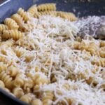 Adding cheese to pasta in pan.