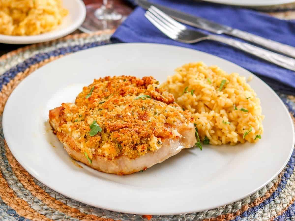 blue cheese topped pork chops on a white plate with a risotto