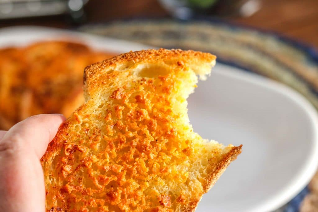Closeup of crunchy cheesy garlic bread with a bit taken out with white serving dish in background.