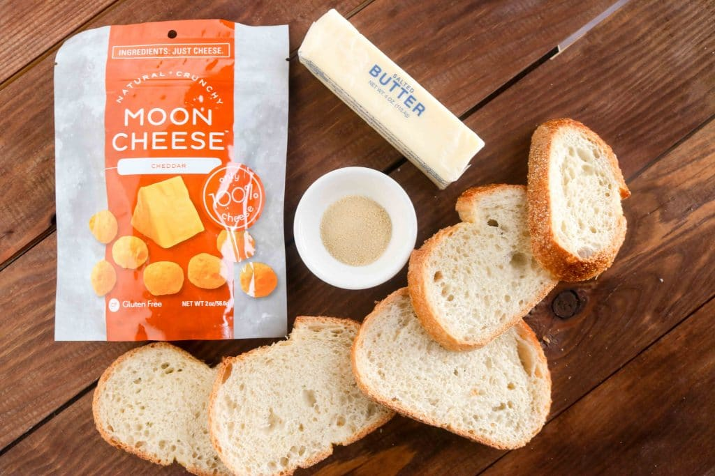 Sliced bread, stick of butter, garlic powder in small white bowl, and package of Moon Cheese on a wood table.