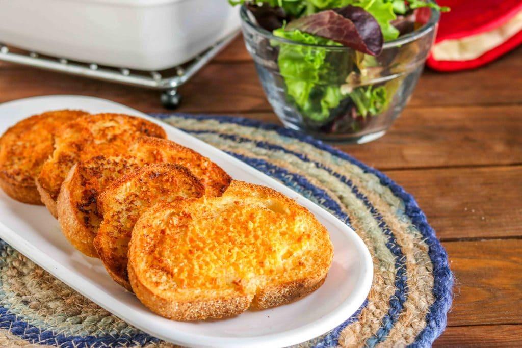 crunchy cheesy garlic bread - horizontal, white plate