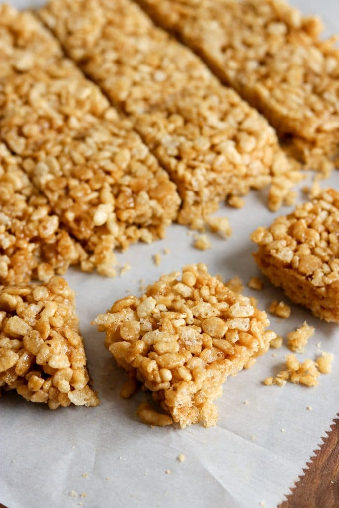 Caramel rice krispie treats cut into squares on parchment paper.
