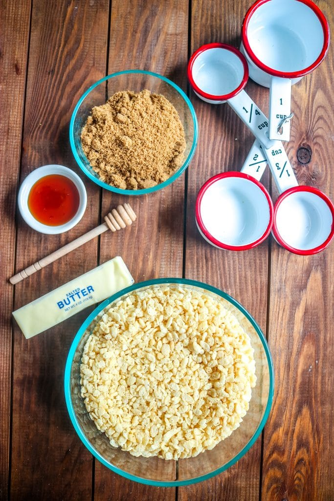 Overhead shot of caramel rice krispie treat ingredients in individual bowls with measuring cups and stick of butter on wood table.