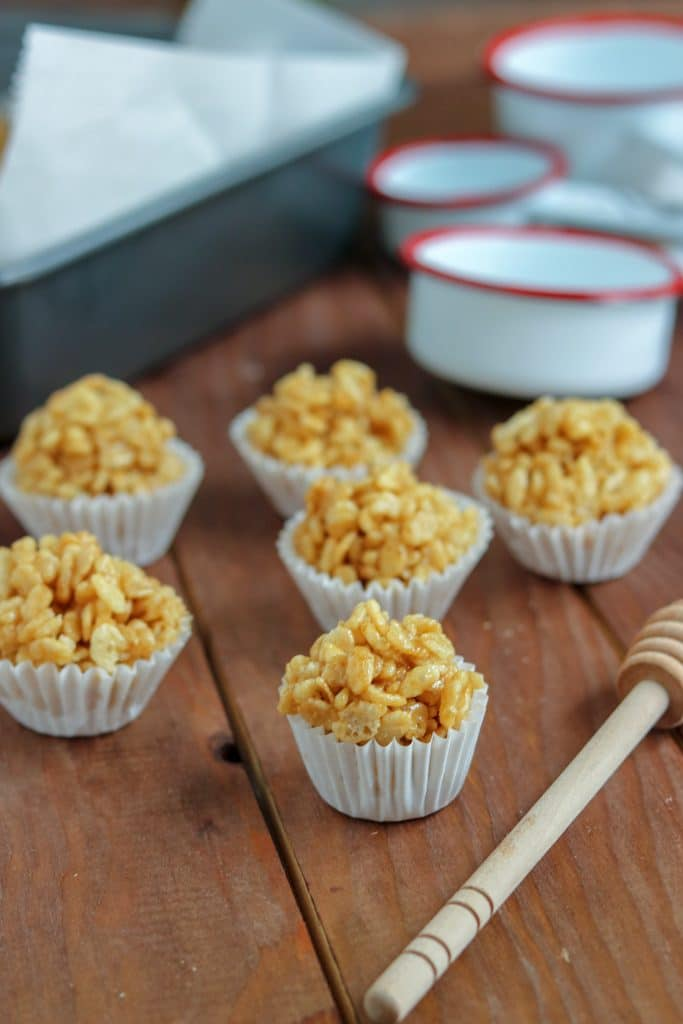 Caramel rice krispies in paper cups with measuring cups in background on wood table.